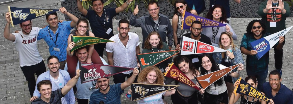 Group of college students with school pennants.